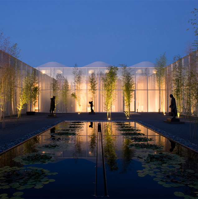 Reflecting pool at the NC Museum of Art at dusk surrounded by sculptures.