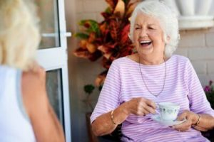 Happy woman enjoying a cup of tea and laughing with a friend